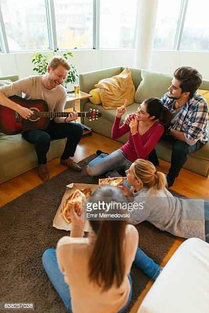 Friends having party with pizza, beer and good music