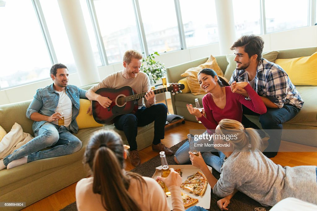 Friends having party with pizza, beer and good music : Stock Photo