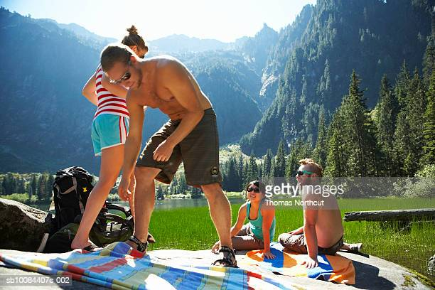 Friends having picnic by lake