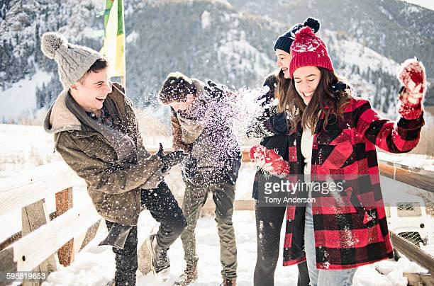 Friends having snow fight outside winter cabin