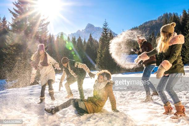 friends having snowball fight out in snow on sunny day - fun stock pictures, royalty-free photos & images