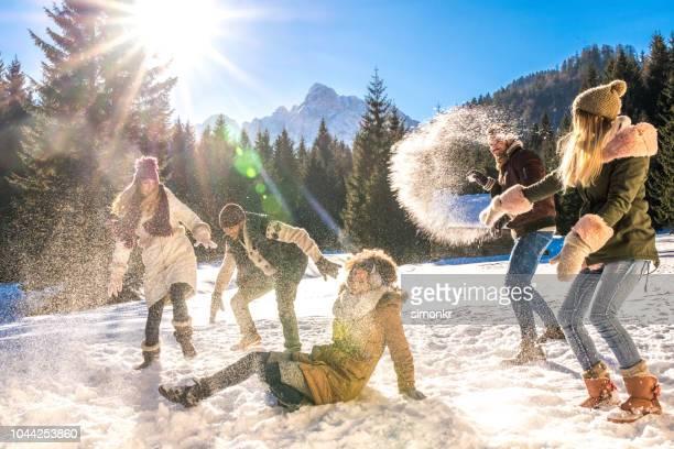 friends having snowball fight out in snow on sunny day - inverno foto e immagini stock