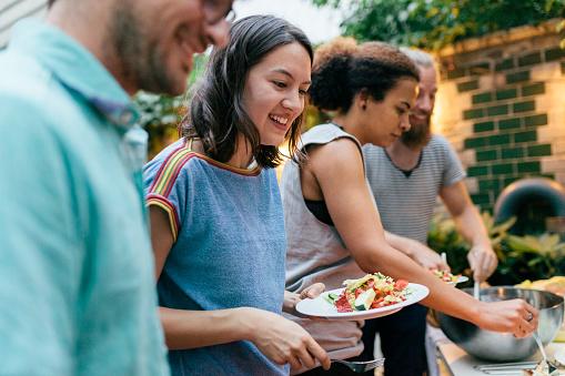Friends Having Summer Barbecue Together Line Up For Food - gettyimageskorea