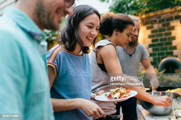 friends having summer barbecue together line up for food - man eating woman out stock photos and pictures