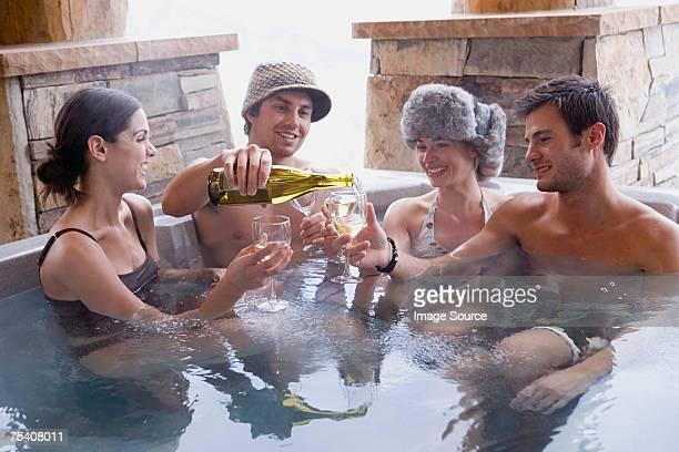 Friends having wine in hot tub