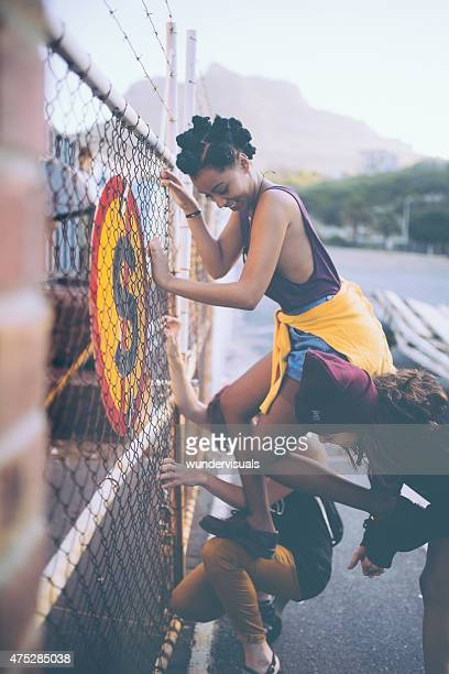 Friends helping Afro grunge girl climb urban fence