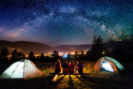 Friends hikers sitting beside camp and tents in the night 678554980
