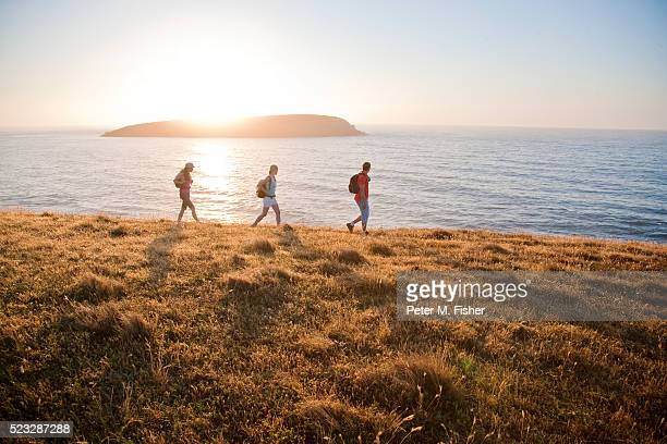 friends hiking beside the sea - peninsula stock pictures, royalty-free photos & images