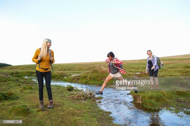 friends hiking in countryside jumping over small stream. - dougal waters stock pictures, royalty-free photos & images