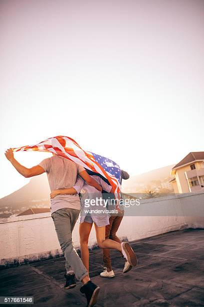 Friends holding American flag over shoulders on roftop