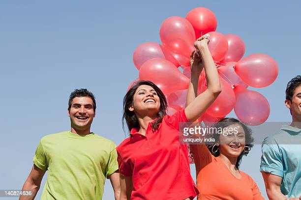 Friends holding balloons and enjoying