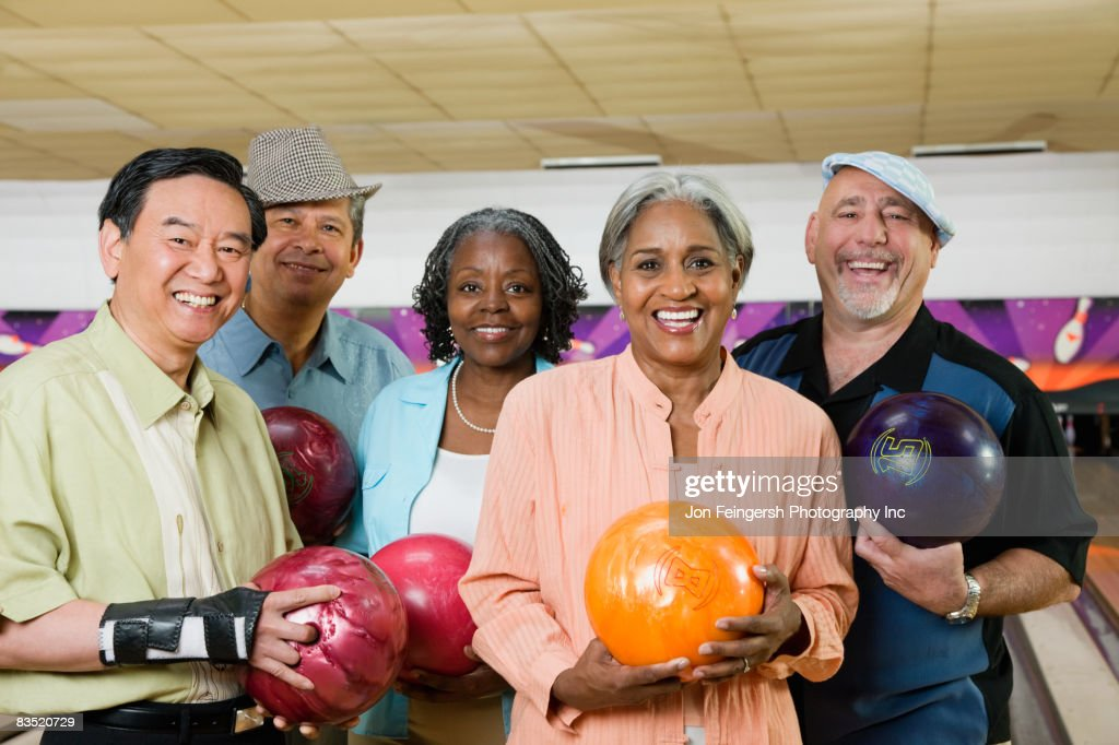 Friends holding bowling balls in bowling alley : Stock Photo
