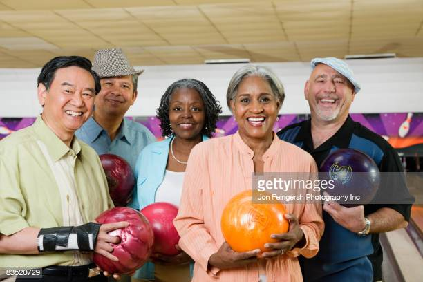 Friends holding bowling balls in bowling alley