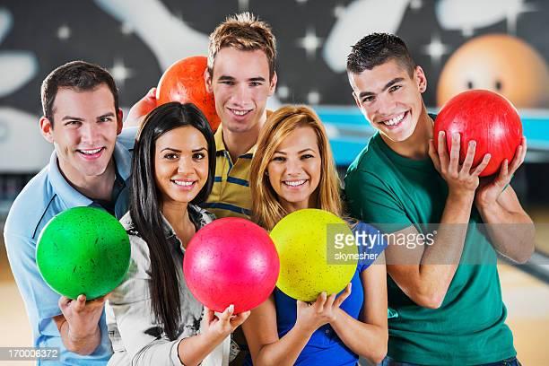 Friends holding bowling balls.