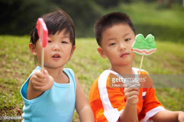 Friends Holding Candies While Sitting On Field At Park