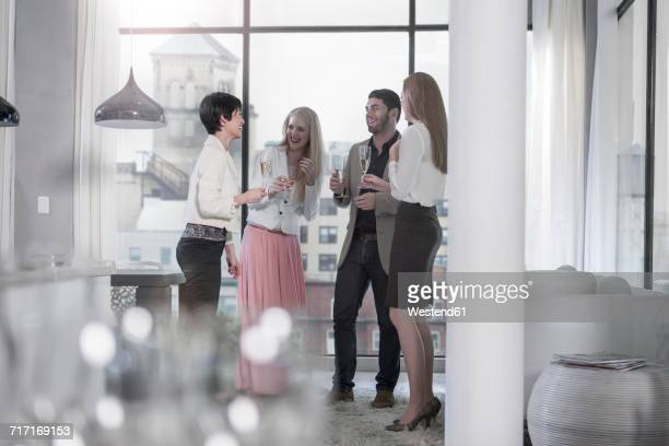 Friends holding champagne glasses socializing in a city apartment