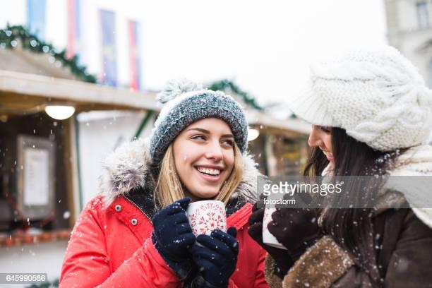 Freunde halten Tassen mit Heißgetränk auf Winter Straße
