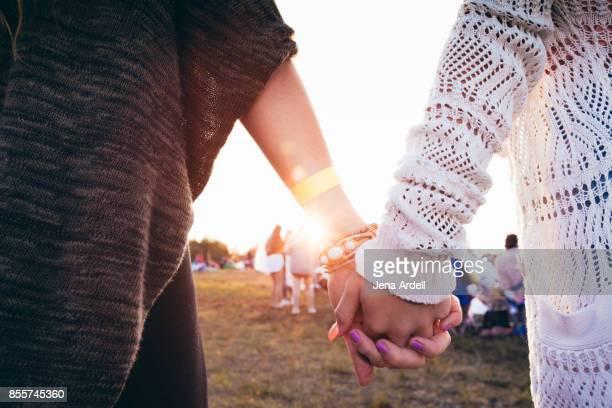 friends holding hands at music festival - armband stock-fotos und bilder