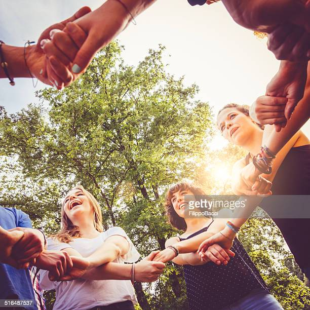 Friends holding hands in the park