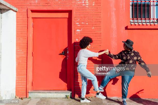 friends holding hands while greeting with foot bumps during sunny day - handshake stock pictures, royalty-free photos & images