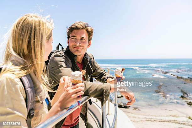 Friends holding ice cream by railing at beach