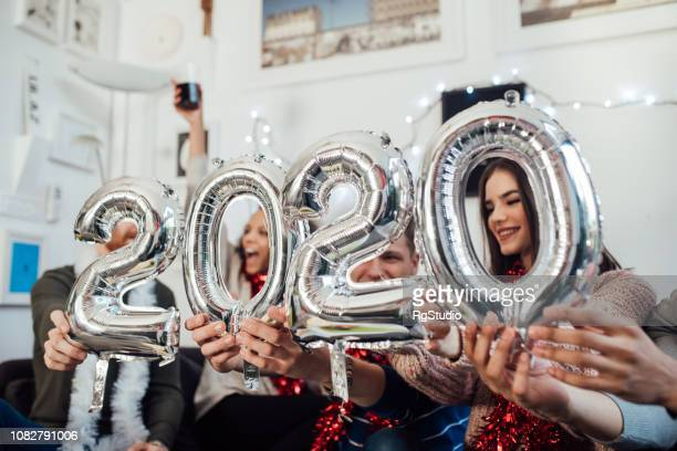 friends holding new year balloons - new year 2020 stock photos and pictures