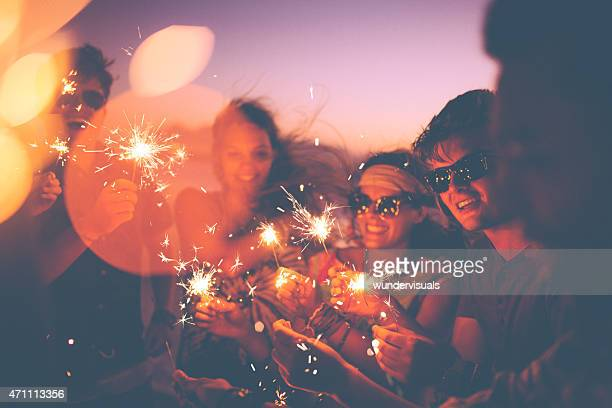 Friends holding sparklers en un beachparty en crepúsculo