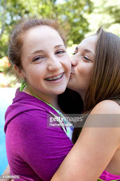 friends hugging and kissing on cheek - only teenage girls stock pictures, royalty-free photos & images