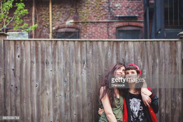 Friends hugging at wooden fence