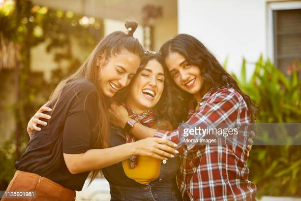 friends hugging each other during garden party - three people foto e immagini stock