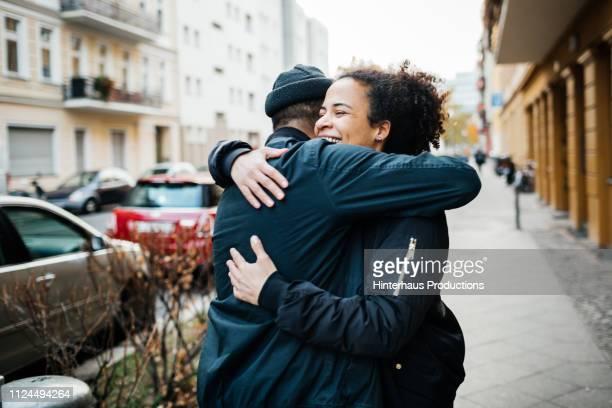 friends hugging in the street - umarmen stock-fotos und bilder