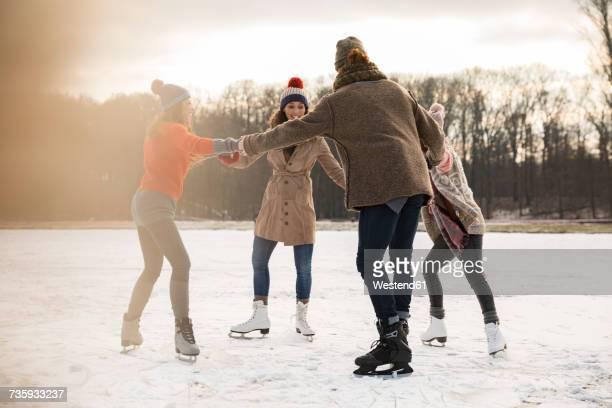 friends ice skating in a circle on frozen lake - schaats ijs stockfoto's en -beelden