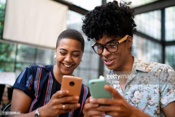 amici in un bar che guardano video divertenti al cellulare - navigare in internet foto e immagini stock