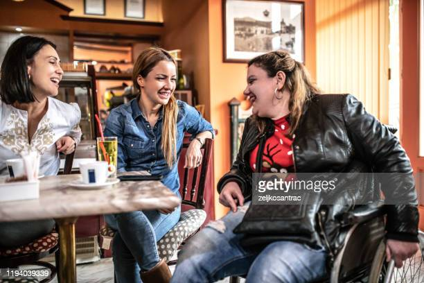 friends in a cafe, the woman  sitting in wheelchair - persons with disabilities stock pictures, royalty-free photos & images