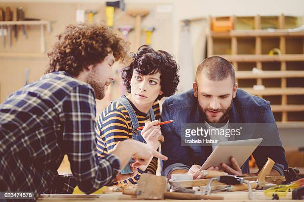 Friends in a construction workshop, discussing over digital tablet