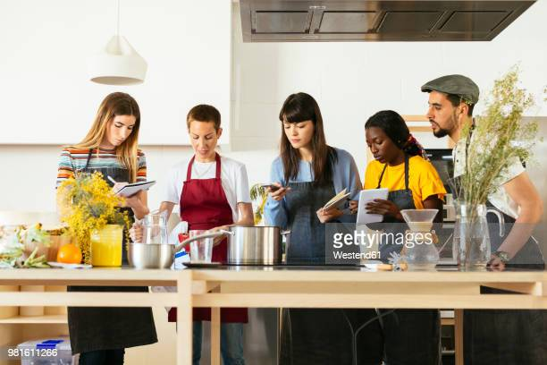friends in a cooking workshop listening to instructor - electric stove burner stock pictures, royalty-free photos & images
