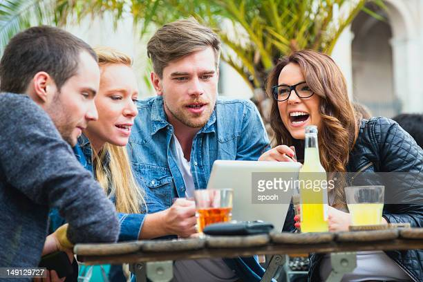 Amici che si diverte nel bar guardando un tablet.