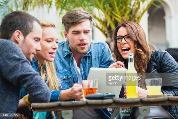 Friends in bar having fun watching tablet.
