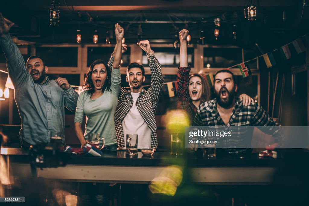 Friends in bar watching game : Stock Photo