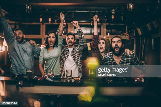 friends in bar watching game - match sport stock pictures, royalty-free photos & images