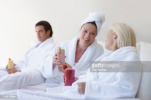 Friends in bathrobes drinking smoothies at spa