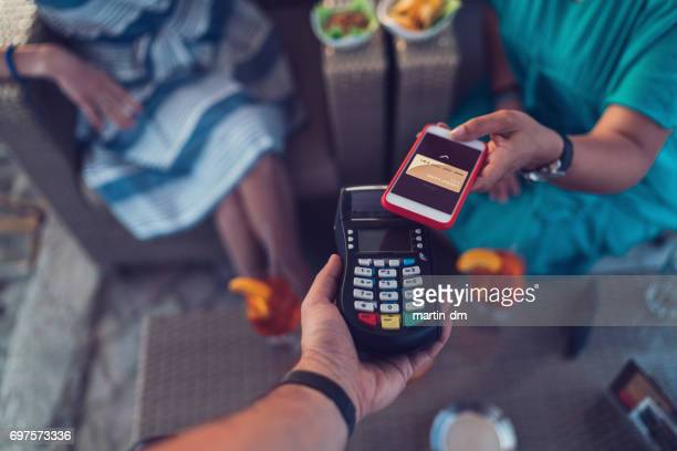 Friends in cafe paying contactless with smartphone