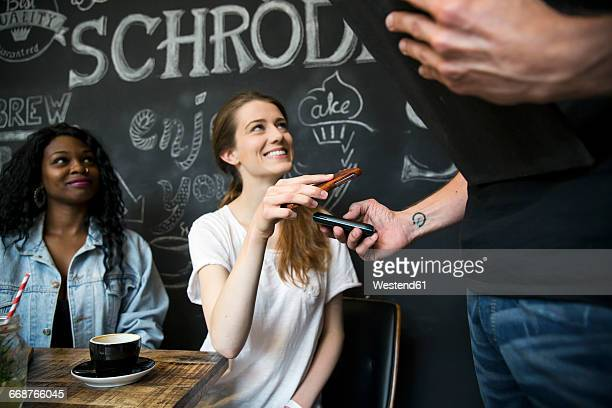 Friends in cafe paying with smartphone