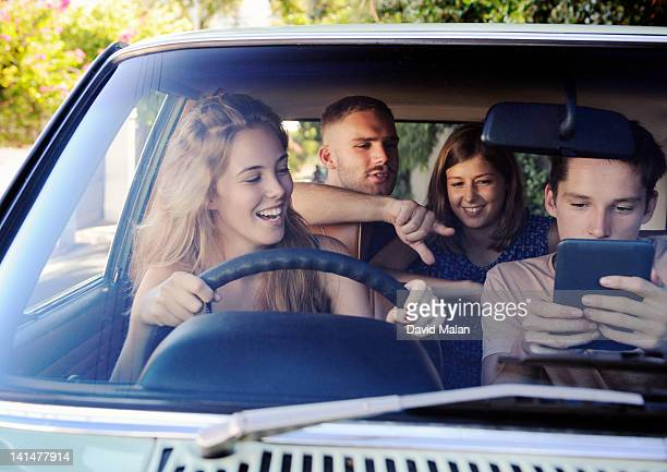 Friends in car looking at a tablet computer
