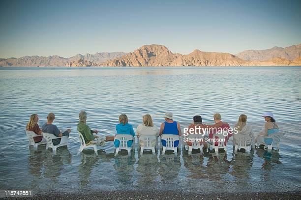 friends in chairs in the water at sunset - halbinsel niederkalifornien stock-fotos und bilder