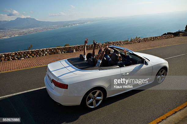 4 friends in convertible car with raised hands - convertible stock photos and pictures