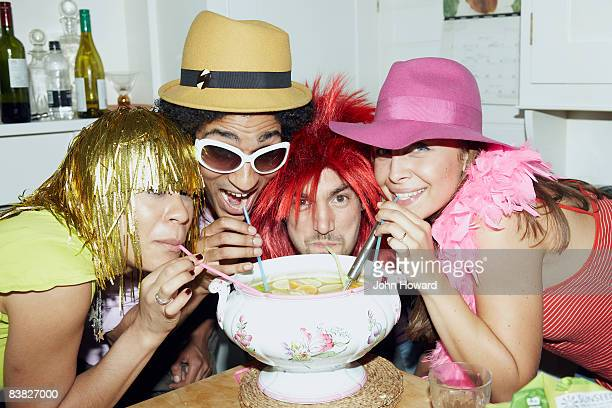 Friends in costume drinking punch through straws