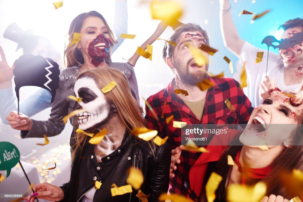Friends in creepy costumes having fun at Halloween party : Stock Photo