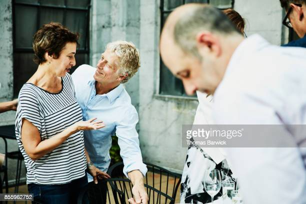 Friends in discussion while being seated for celebration dinner on restaurant patio