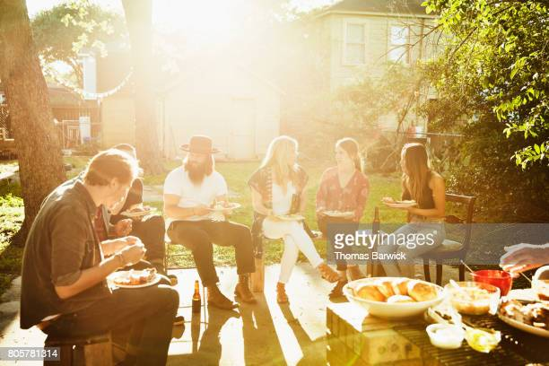 Friends in discussion while eating dinner in backyard on sunny summer evening
